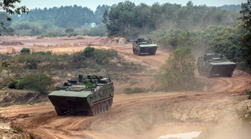 Armored vehicles rumble to training field