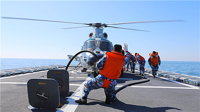Sailors refuel ship-borne helicopter on flight deck