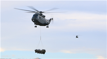 Z-8 helicopter lifts military vehicle