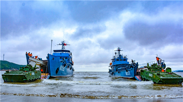 Armored vehicles wade ashore from landing ships at beachhead