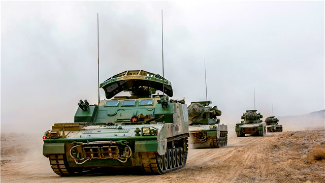 Armored vehicles maneuver in hinterland of Qilian Mountains