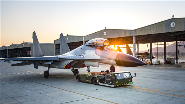 Pushback tractor moves a J-11 fighter jet