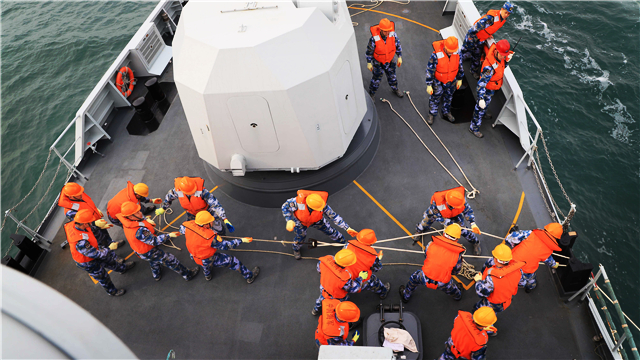 Sailors heave the mooring lines aboard frigate