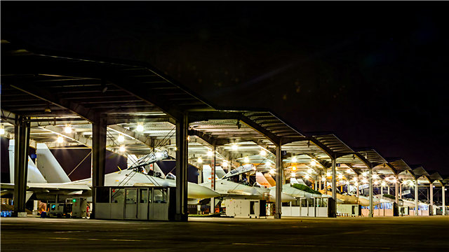 Fighter jets sit abreast in aircraft hangars