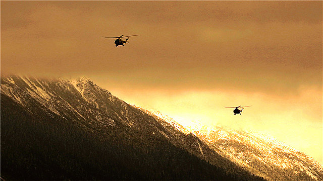 Transport helicopters fly in formation over mountains