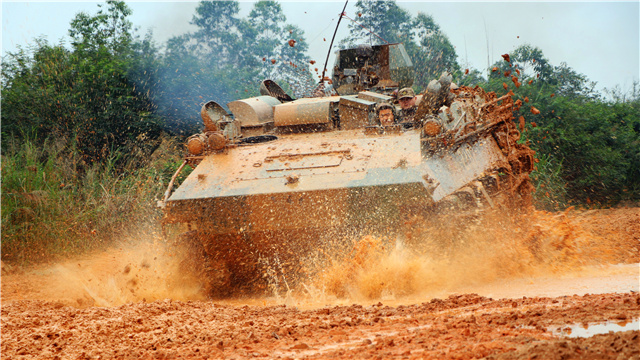 Infantryman drives armored vehicle through mud puddle