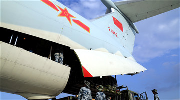 Airmen load cargo into transport aircraft