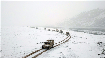 Military trucks pass through snow-covered roads
