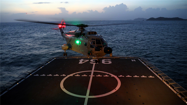 Ship-borne helicopter hovers over before landing