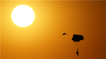 Paratroopers dive from transport aircraft