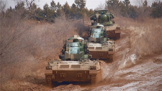 Armored vehicles maneuver on rugged mountain road