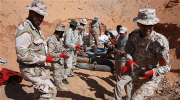 Fighters of UN-backed Libyan government move explosive remnants in old military camp in Libya