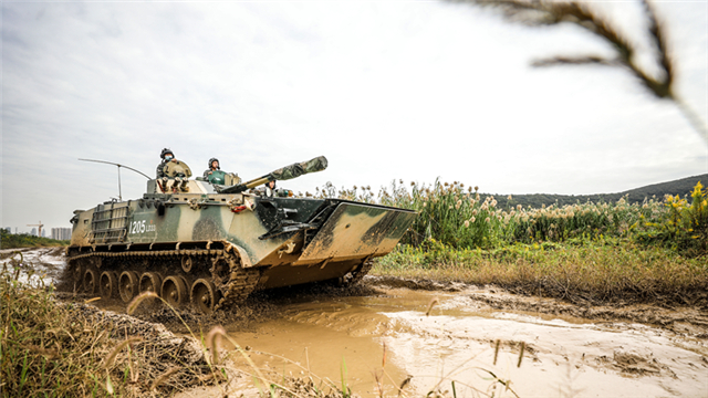 Infantry fighting vehicles drive through mire
