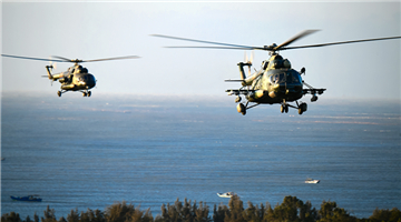 Helicopters hover above sea