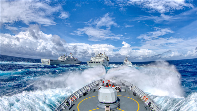 Warship formation performs replenishment-at-sea