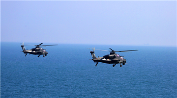 Attack helicopters hover above sea