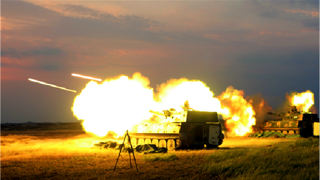 Self-propelled howitzer systems fire at targets